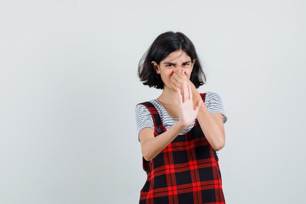Preteen girl pinçant son nez en t-shirt