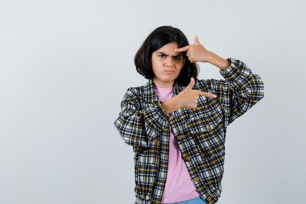 Preteen girl pointant à gauche et à droite en chemise, veste, vue de face.