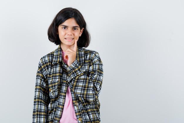 Preteen girl pointant sur son sourire en chemise, veste, vue de face.