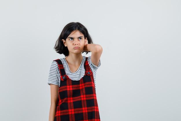 Preteen girl tenant la main sur la tête en t-shirt