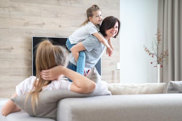 Preteen triste fille assise sur le canapé pendant que la mère s'amuse avec la sœur cadette, le concept de la jalousie