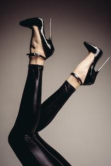 Prêteur de jambes féminines en combinaison de spandex et d'une chaussure fétiche avec des talons extrêmement hauts. thème bdsm.