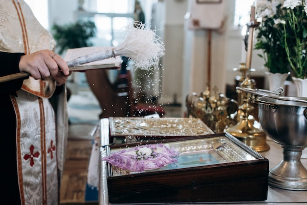 Un prêtre arrose de l'eau bénite sur des alliances à l'église
