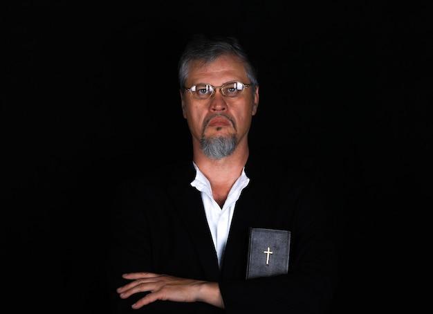 Prêtre avec la bible sur fond noir
