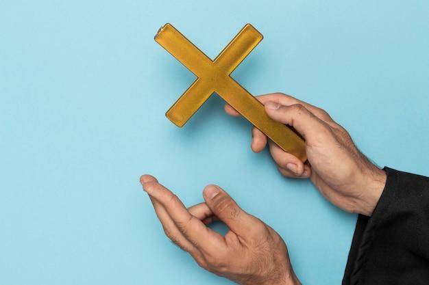 Prêtre avec un doigt croisé et une croix en bois