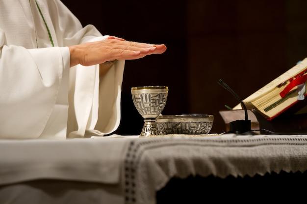 Prêtre mains sur le calice pendant la messe