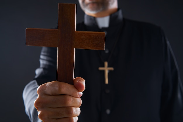 Un prêtre tenant une croix de bois en prière