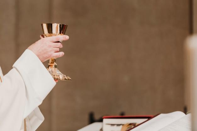 Prêtre tenant le gobelet lors d'une messe nuptiale de cérémonie de mariage. concept de religion