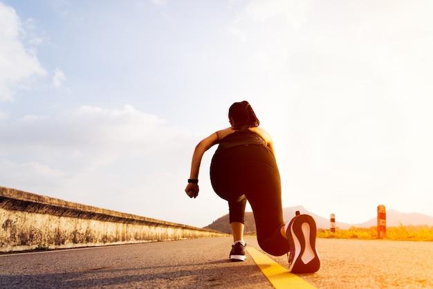 Prêts partez. femme en cours d'exécution sur la position de départ et va courir sur une longue route