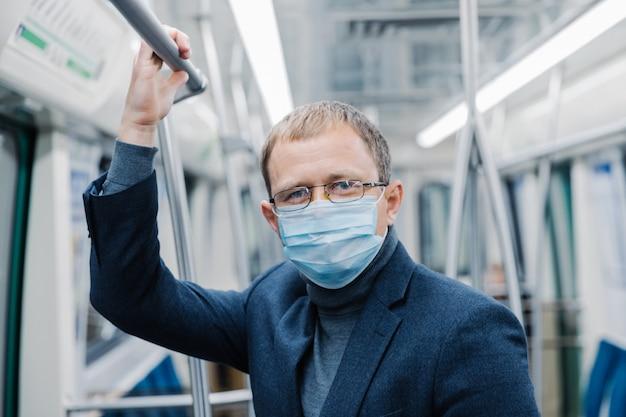 Prévention du coronavirus. un employé de bureau porte des lunettes transparentes, une tenue formelle, un masque médical, ñ ares sur la sécurité, pose dans le métro, se déplace dans les transports publics pendant l'épidémie de covid-19.