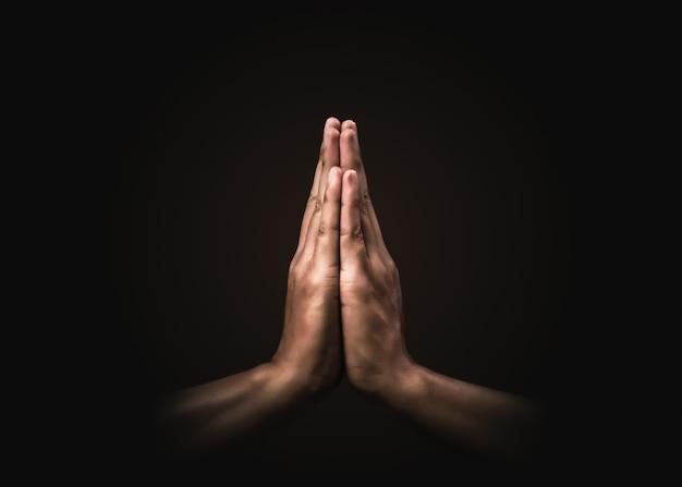 Prier les mains avec la foi en la religion et la croyance en dieu dans l'obscurité. puissance d'espoir ou d'amour et de dévotion. namaste ou namaskar geste des mains. position de prière.