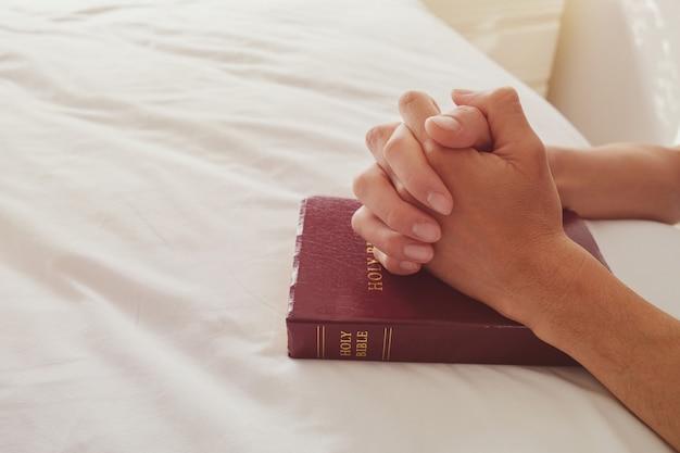 Prier les mains avec un livre de bible sur un lit blanc