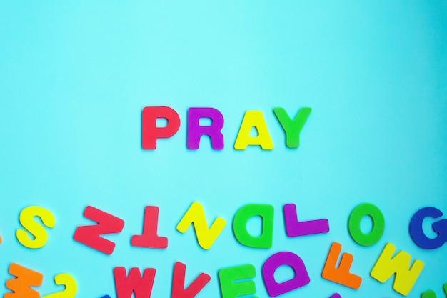 Prier de mot fait de lettres colorées sur le mur bleu.