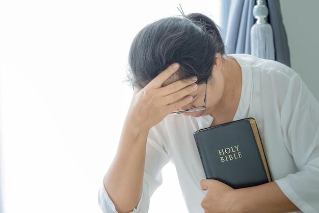 Prière de crise de la vie chrétienne à dieu. femme priez pour que dieu bénisse et souhaite avoir une vie meilleure. mains de femme priant dieu avec la bible. implorer le pardon et croire en la bonté.