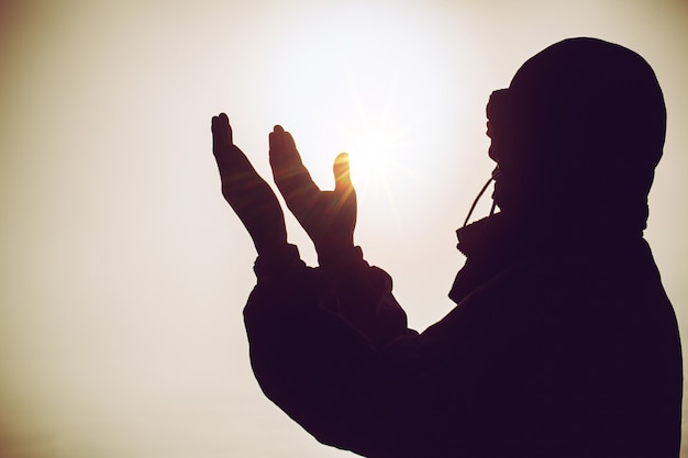 Prière spirituelle mains sur le soleil brille avec beau coucher de soleil floue