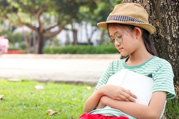 Primaire fille assise lisant un livre jusqu'à dormir, allongée sous l'arbre