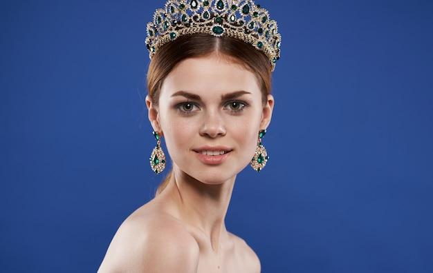 Princesse avec couronne sur sa tête et maquillage de boucles d'oreilles.