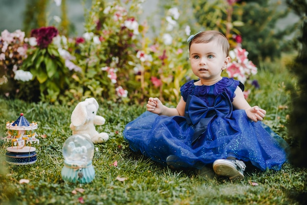 Princesse étonné bébé fille avec robe bleue assise sur l'herbe avec ses jouets et regardant quelqu'un