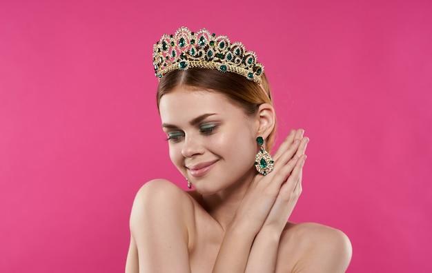 Une princesse romantique avec un diadème sur la tête touche son visage avec ses mains sur un fond rose. photo de haute qualité