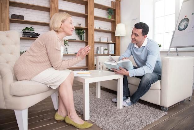 Principaux conseils. psychologue senior gay parlant pendant que l'homme étudie le livre