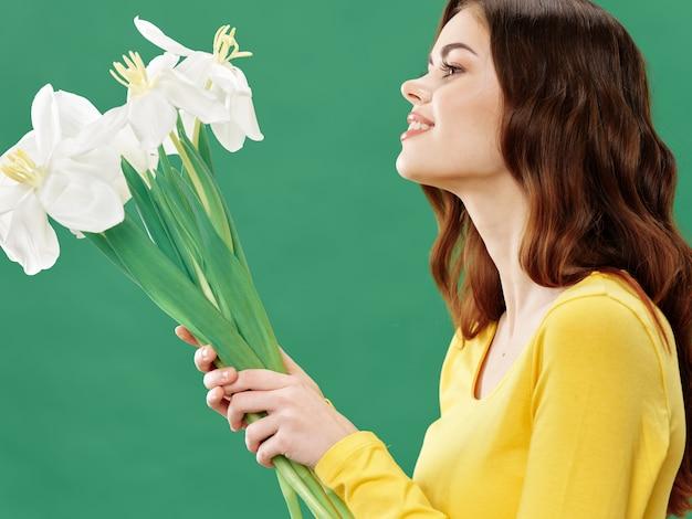 Printemps belle jeune fille avec des fleurs sur un studio coloré. femme posant avec un bouquet de fleurs.