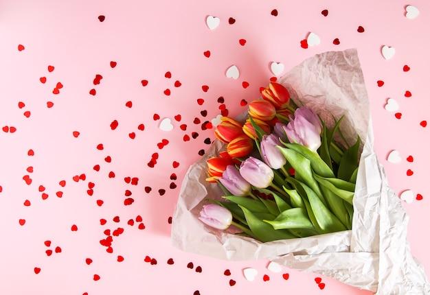 Printemps de belles fleurs de tulipes sur fond rose pastel doux avec des guirlandes de coeur rouge. fête des mères, carte de voeux composition florale décorative festive.