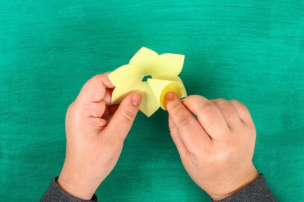 Printemps bricolage jonquilles fleurs de papier jaune sur fond vert.