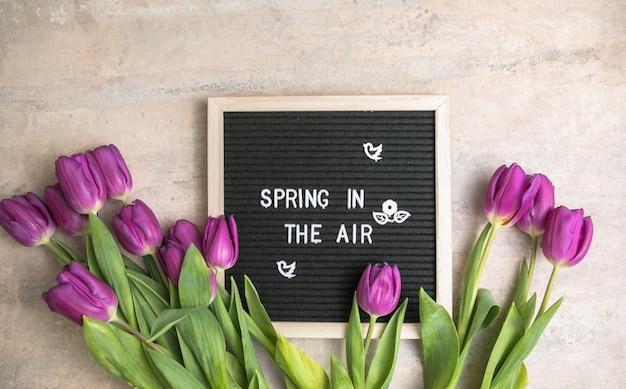 Le printemps dans l'air sur carton à lettres et bouquet de fleurs de tulipes violettes