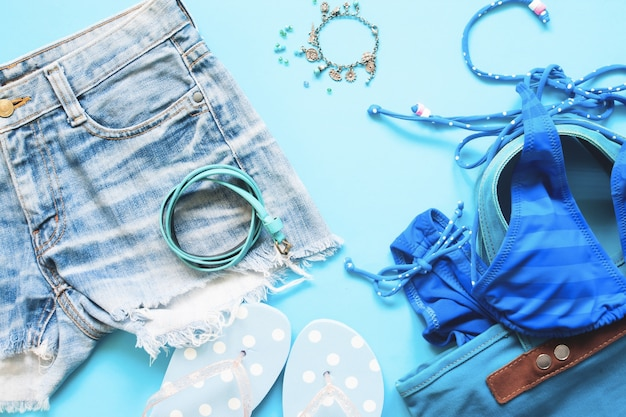 Le printemps et l'été, collection bleue d'accessoires pour filles, flat lay on blue background