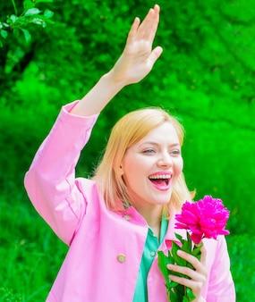 Printemps. femme heureuse avec fleur de pivoine, agitant la main. fille souriante accueillant les amis.