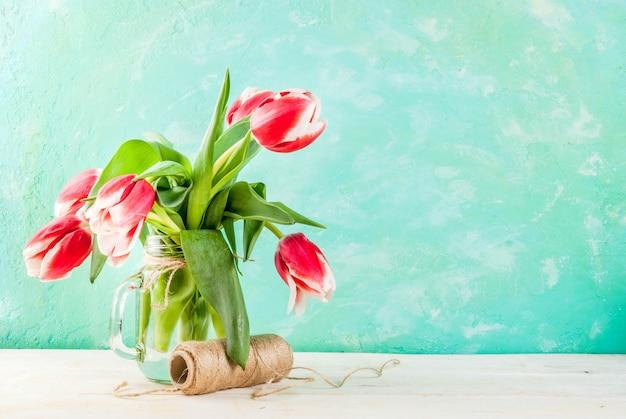 Printemps . fleurs de tulipes dans un bocal en verre, sur un fond bleu clair et bois blanc.
