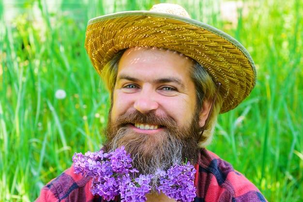 Printemps. homme barbu souriant avec des fleurs dans la barbe. barbe hipster avec des fleurs. publicité de salon de coiffure. style de barbe.