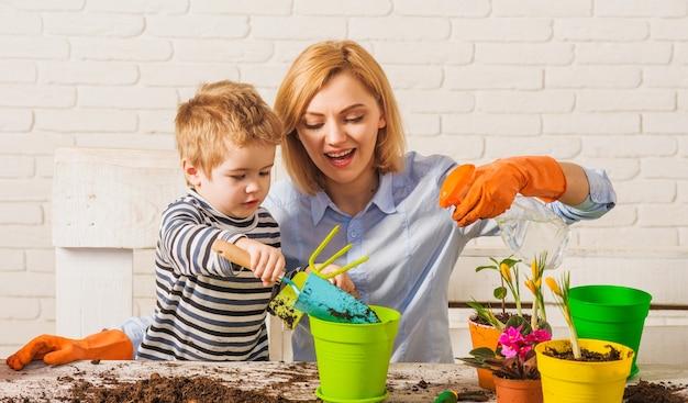 Printemps. mère avec petit fils plantant une fleur. relations de famille. soin des plantes. jardinage