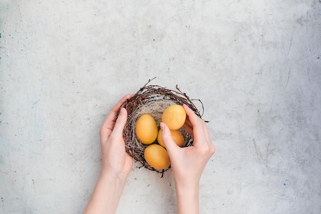 Printemps pâques des mains féminines tiennent un nid avec des oeufs colorés de pâques. composition abstraite de la vue horizontale supérieure. abstrait
