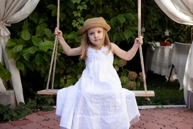 Printemps, petite fille sur la balançoire dans le parc