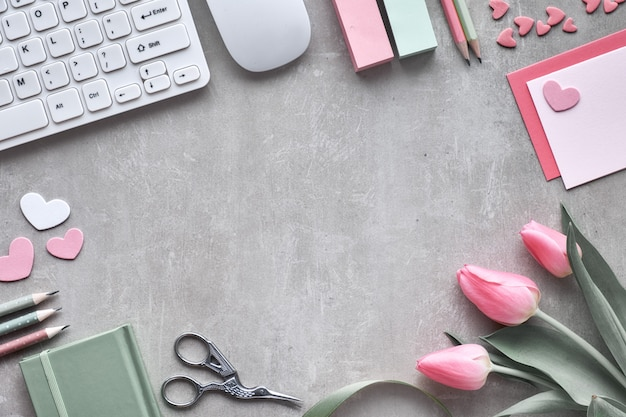 Printemps plat poser avec clavier, souris, tulipes roses, papeterie, cartes de souhaits et coeurs décoratifs