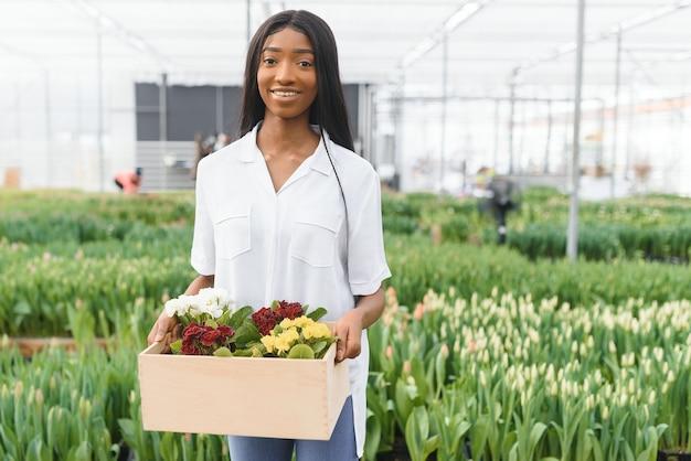 Printemps et semis. souriante fille afro-américaine en tablier porte une boîte avec de jeunes plantes sur fond de fleurs à l'intérieur de la serre
