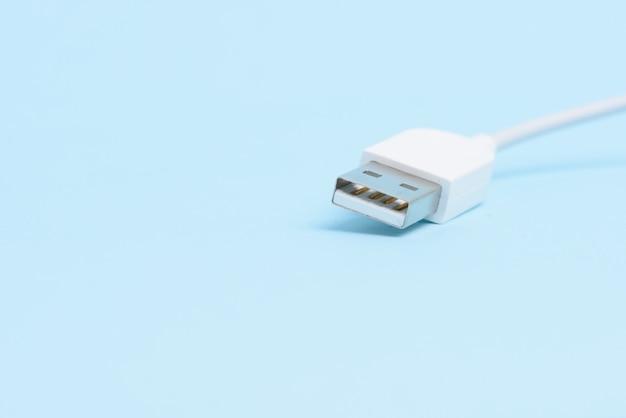 Une prise de câble usb blanche isolée sur fond bleu clair.