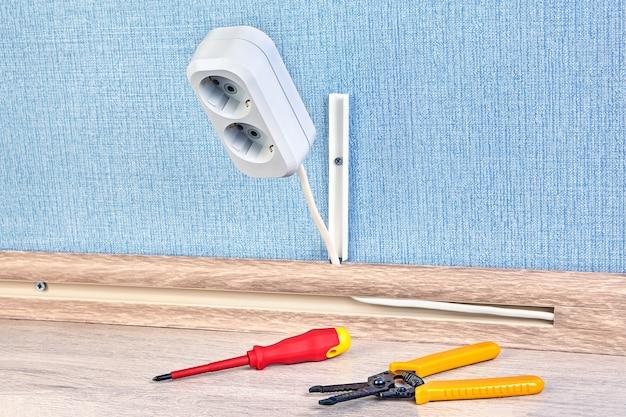 Prise de courant duplex avec tournevis et coupe-fil à dénuder à proximité.