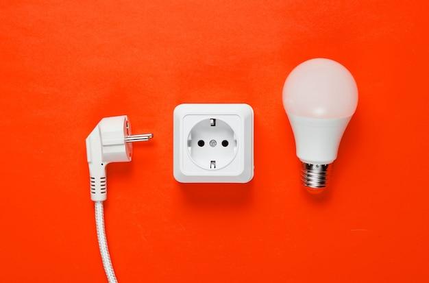 Prise de courant en plastique blanc, prise d'alimentation, ampoule led sur fond orange. vue de dessus