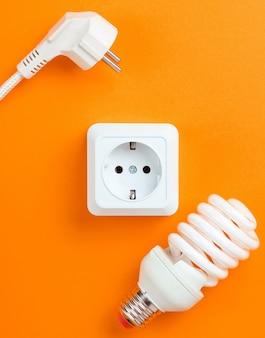Prise de courant en plastique blanc, prise d'alimentation, ampoule en spirale sur fond orange. vue de dessus