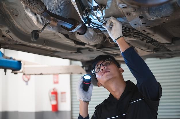Prise mécanique asiatique et lampe de poche brillante pour examiner la voiture sous le châssis