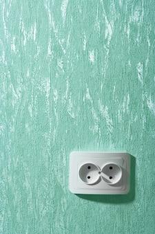Prise murale électrique à un mur vert
