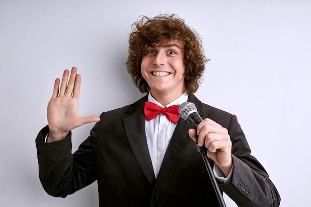 Prise de parole en public de l'artiste disant bonjour à tous et souriant, portant un costume noir et une cravate papillon rouge