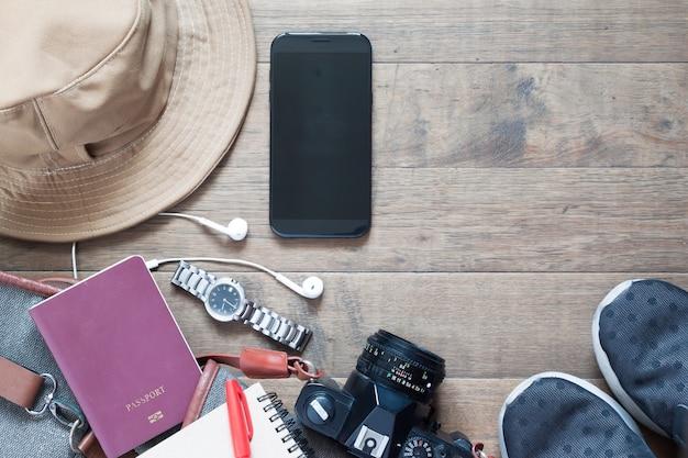 Prise de vue aérienne des articles de voyage et accessoires avec appareil mobile sur fond en bois, pose plate d'articles d'été et de vacances