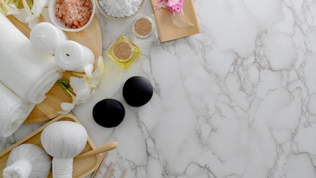 Prise de vue aérienne du concept de traitement de spa de beauté et de détente avec une serviette blanche, du sel de spa, des pierres chaudes et d'autres accessoires de spa