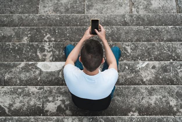 Une prise de vue aérienne d'un homme assis sur l'escalier en béton à l'aide de son smartphone