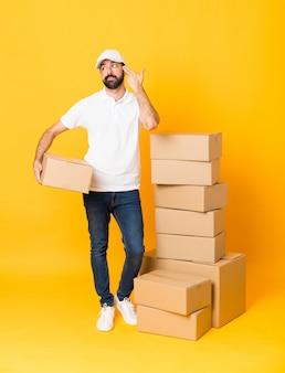 Prise de vue complète du livreur parmi les boîtes sur fond jaune isolé