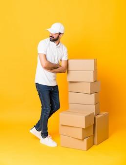 Prise de vue complète du livreur parmi des boîtes isolées de jaune avec les bras croisés et heureux