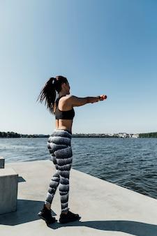 Prise de vue complète d'une femme faisant de l'exercice au bord du lac